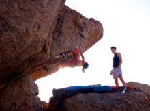 Bouldern am Fels, zwei Personen im Gegenlicht.