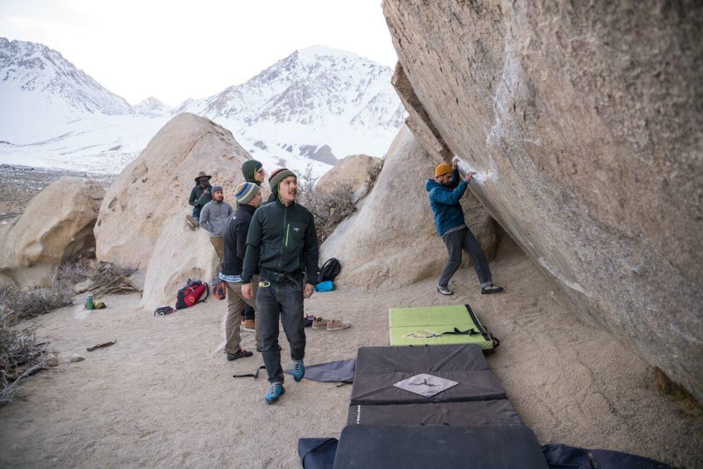 Bouldern draußen am Fels. Fünf Personen im Gebirge